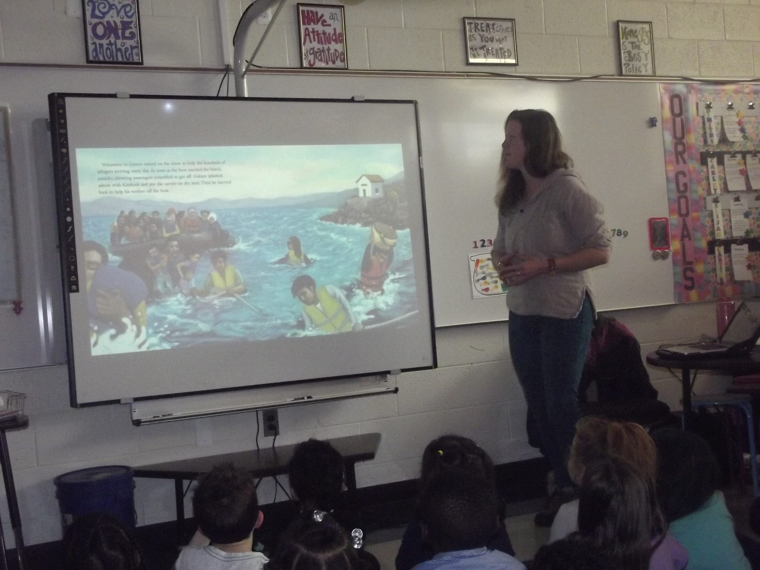 Co-Author and Character Amy Shrodes describes one of the pages on a screen in an elementary school classroom.