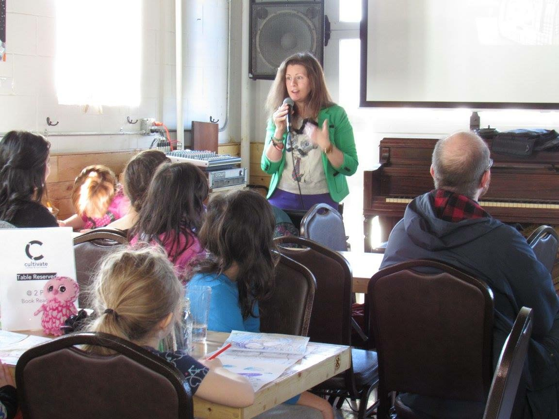 Co-Author and Character Amy Shrodes reads the story at a coffee shop to an all-ages group.